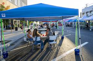 People dine and drink under tents during Dine Out Downtown on California Avenue between Main Street and Casino Center Boulevard Thursday, May 21, 2020.