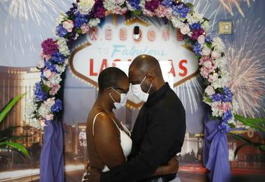 Vaughan Chambers and Alicia Funk put the face coverings on shortly after they exchanged vows and kissed in front of a neon-lit sign in a Las Vegas wedding chapel and posed for photos with an Elvis impersonator who officiated at their wedding.