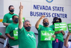 Harry Schiffman, left, president of the American Federation of State County Municipal Employees (AFSCME) union, local 4041, speaks during a rally in front of the Nevada State Business Center on West Sahara Avenue Saturday, June 27, 2020. AFSCME members say Governor Steve Sisolak violated a 2019 collective bargaining statute by refusing to negotiate the furloughs and salary freezes enacted to cut spending amid the coronavirus pandemic.