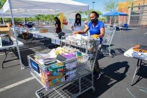 Devoni Mills-Catchings, a site coordinator with Communities in Schools, collects donations during their annual Fill The Bus school supply drive, Friday July 31, 2020.