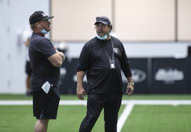 Las Vegas Raiders head coach Jon Gruden, left, talks with defensive coordinator Paul Guenther during an NFL football training camp practice Tuesday, Aug. 25, 2020, in Henderson, Nev. (Chase Stevens/Las Vegas Review-Journal via AP, Pool)