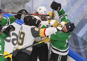 Dallas Stars' Jamie Benn (14) and Vegas Golden Knights' Alex Tuch (89) and Mark Stone (61) battle along the boards during the first period of Game 3 of the NHL hockey Western Conference final, Thursday, Sept. 10, 2020, in Edmonton, Alberta.