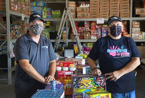Greg Bortles, left, a board member, and Dale Darcas, founder and executive director, pose with donated food in the Serving Our Kids Foundation warehouse in Henderson Saturday, Sept. 12, 2020.