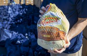 Clark County Commissioner Justin Jones holds a frozen turkey before ...