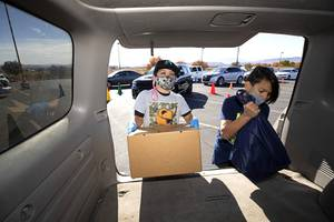 Jude Romero, 11, left, and Liam Jones, 10, load a food box and a frozen turkey into a vehicle during a Thanksgiving food distribution event in the parking lot of the Desert Breeze Community Center Saturday, Nov. 21, 2020. The event was a partnership between Clark County Commissioner Justin Jones, Three Square and Catholic Charities of Southern Nevada.