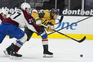 Vegas Golden Knights center William Karlsson (71) attempts a shot around Colorado Avalanche defenseman Ryan Graves (27) during the second period of an NHL hockey game Sunday, Feb. 14, 2021, in Las Vegas.