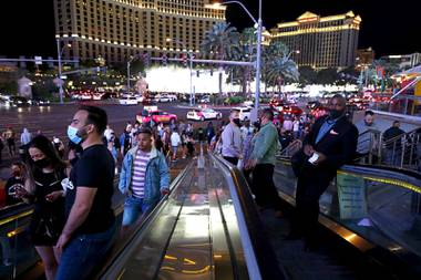 Tourists ride escalators to Planet Hollywood and the Miracle Mile Shops on the Las Vegas Strip Saturday, April 17, 2021.