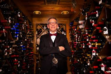 "Jon Simmons, longtime sommelier at Hugo's Cellar at Four Queens, is shown Thursday, April 29, 2021. He says, ""There's nothing more fun than sharing a bottle of wine with somebody who appreciates wine."""