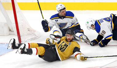 Vegas Golden Knights defenseman Alex Pietrangelo (7) falls with St. Louis Blues left wing Zach Sanford (12) and center Ivan Barbashev (49) in the third period of a game at T-Mobile Arena Saturday, May 8, 2021. Pietrangelo was penalized for tripping.