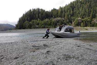 In this March 5, 2020, file photo, Hunter Maltz, a fish technician for the Yurok tribe, pushes a jet boat into the low water of the Klamath River at the confluence of the Klamath River and Blue Creek as Keith Parker, as a Yurok tribal fisheries biologist, watches near Klamath, Calif., in Humboldt County. California Gov. Gavin Newsom on Monday, May 10, 2021, declared a drought emergency for most of California, extending a previous order that affected two counties to 41 counties throughout much of the state.