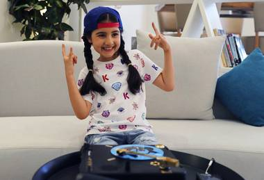 Michelle Rasul flashes a rockstar sign in the lobby of her apartment building in Dubai, United Arab Emirates, Sunday, May 9, 2021. Rasul, a 9-year-old girl from Azerbaijan who lives in Dubai, is scratching her way to the top as a DJ after competing in the DMC World DJ Championship.